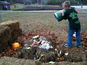 An elementary school student constructing a compost pile using food waste from the cafeteria. (http://inspiredowl.org/2010/10/25/composting-in-the-lunchroom/)